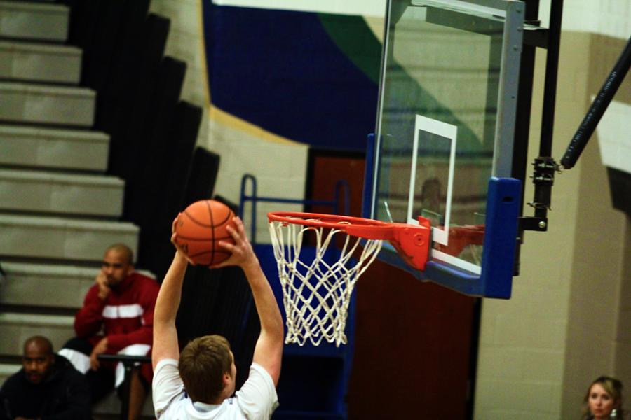 Senior center Connor McClenagan dunks the ball after being left wide open when the Hawks were on the fast-break