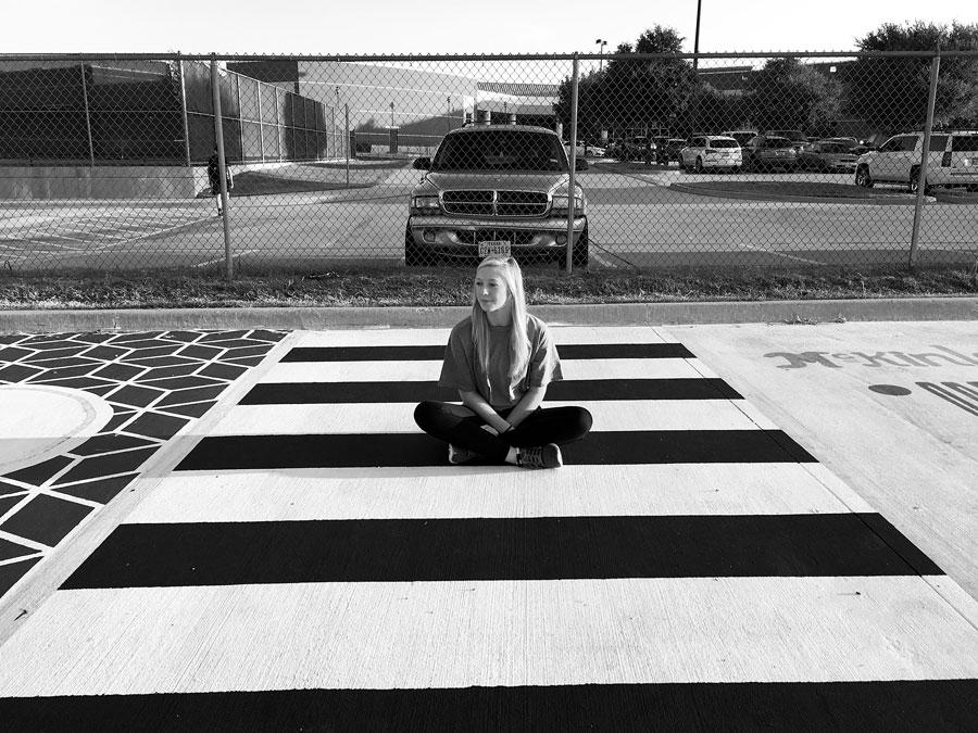 Senior+Avery+Crowe+sits+in+her+parking+spot.+Due+to+her+relapse+in+late+August+of+2016%2C+Avery+lost+memory+of+painting+it.