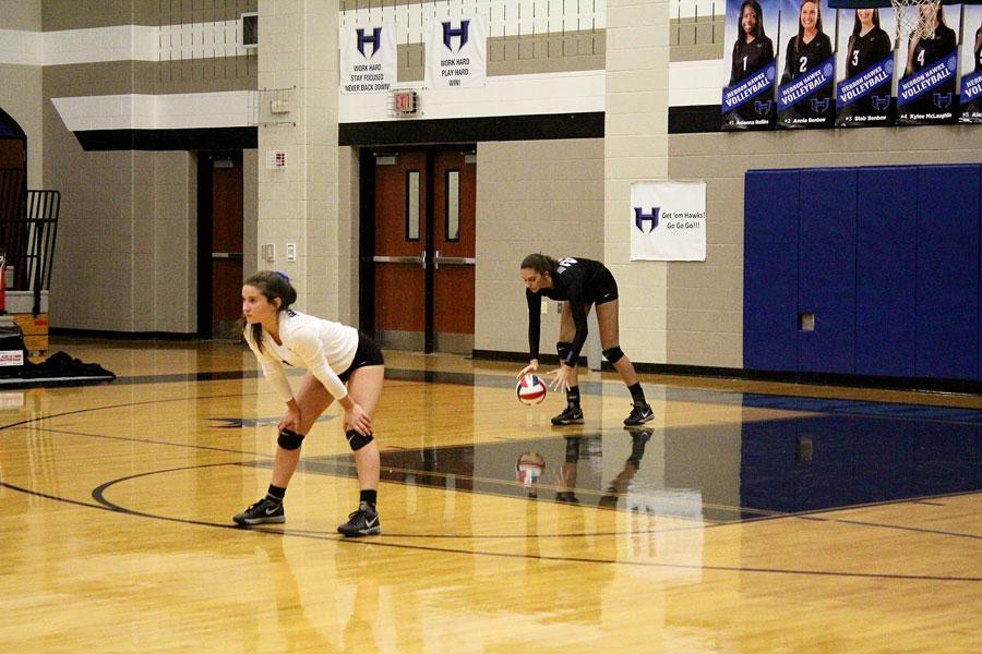 Freshman Nicole Drewnick (Right Side) goes back to serve, while libero Junior Annie Benbow prepares for defense.