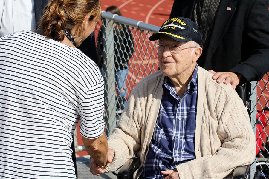A disabled Veteran shakes hands with a teacher who attended the ceremony. He was thanked for his service to the country.