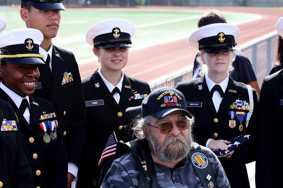 A Vietnam War veteran poses with JROTC after the assembly. The veteran lost both his legs in the war.