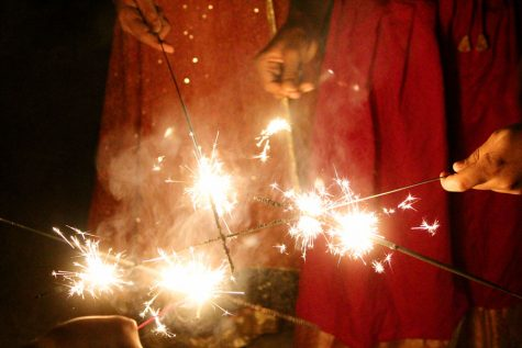 Children light sparklers together as they try to create an explosion of light.