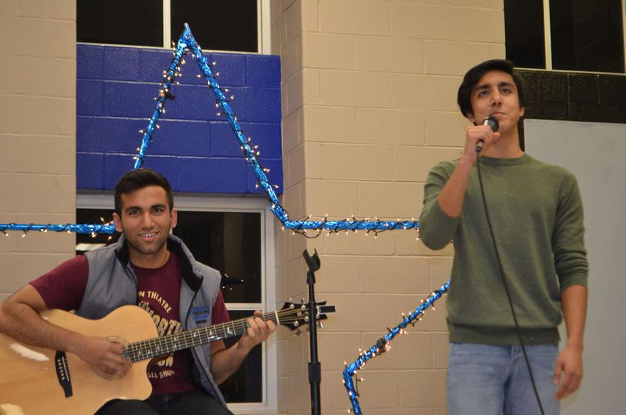 Seniors Mihir Lulay and AJ Abdullah sing and play guitar in a game of Adjective Noun.
