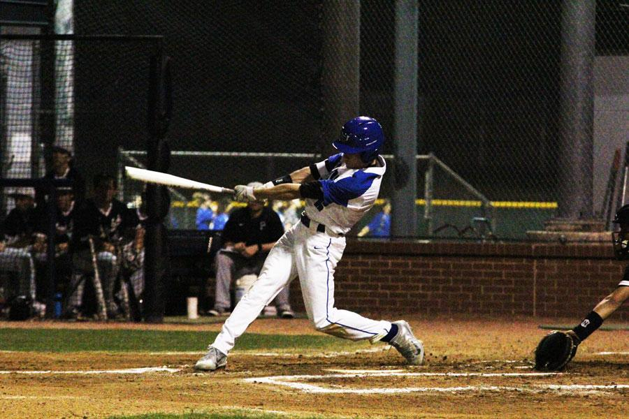 Batter swings for the Hawks. After hitting the ball, he ran and got to first base.
