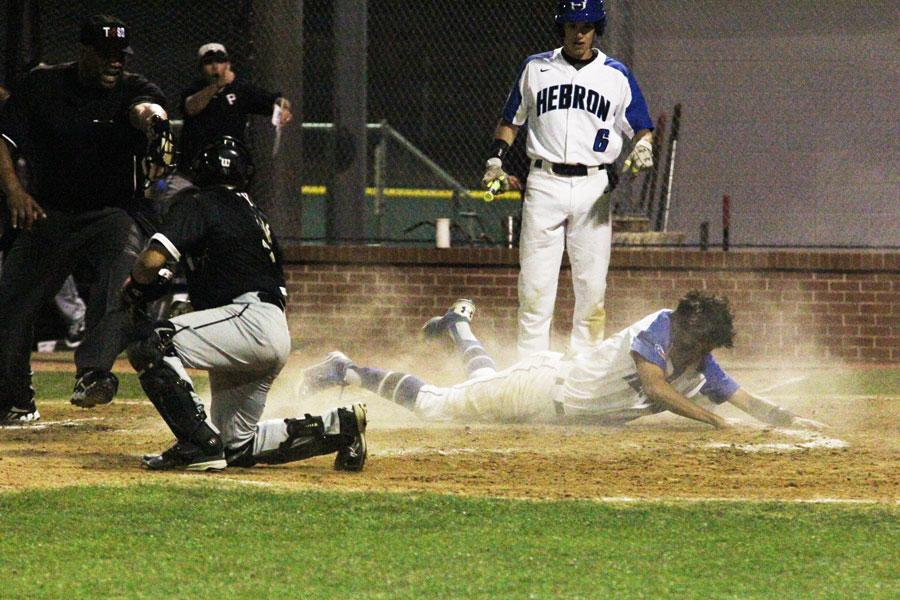 Alec	Eskenazi slides into home. Eskenazi made it safe and scored a run.