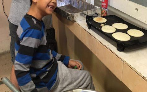 Angel, a resident at Casa Hogar, helps make pancakes for breakfast.