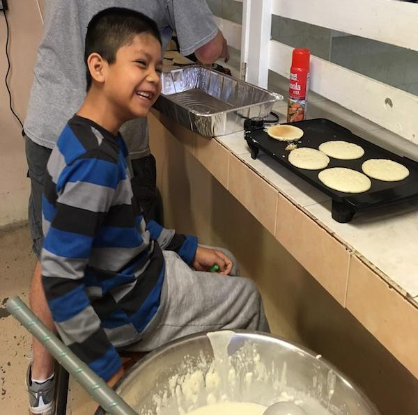 Angel, a resident at Casa Hogar, helps make pancakes for breakfast.
