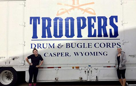 Seniors Juliann Page and Sophie Malis pose by the Troopers' bus. They posted this photo to social media to announce that they were contracted with the drum corps.