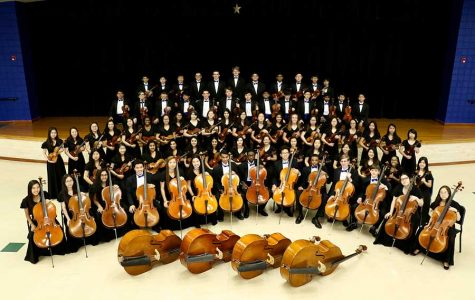 All of the members of the orchestra pose with their instruments.