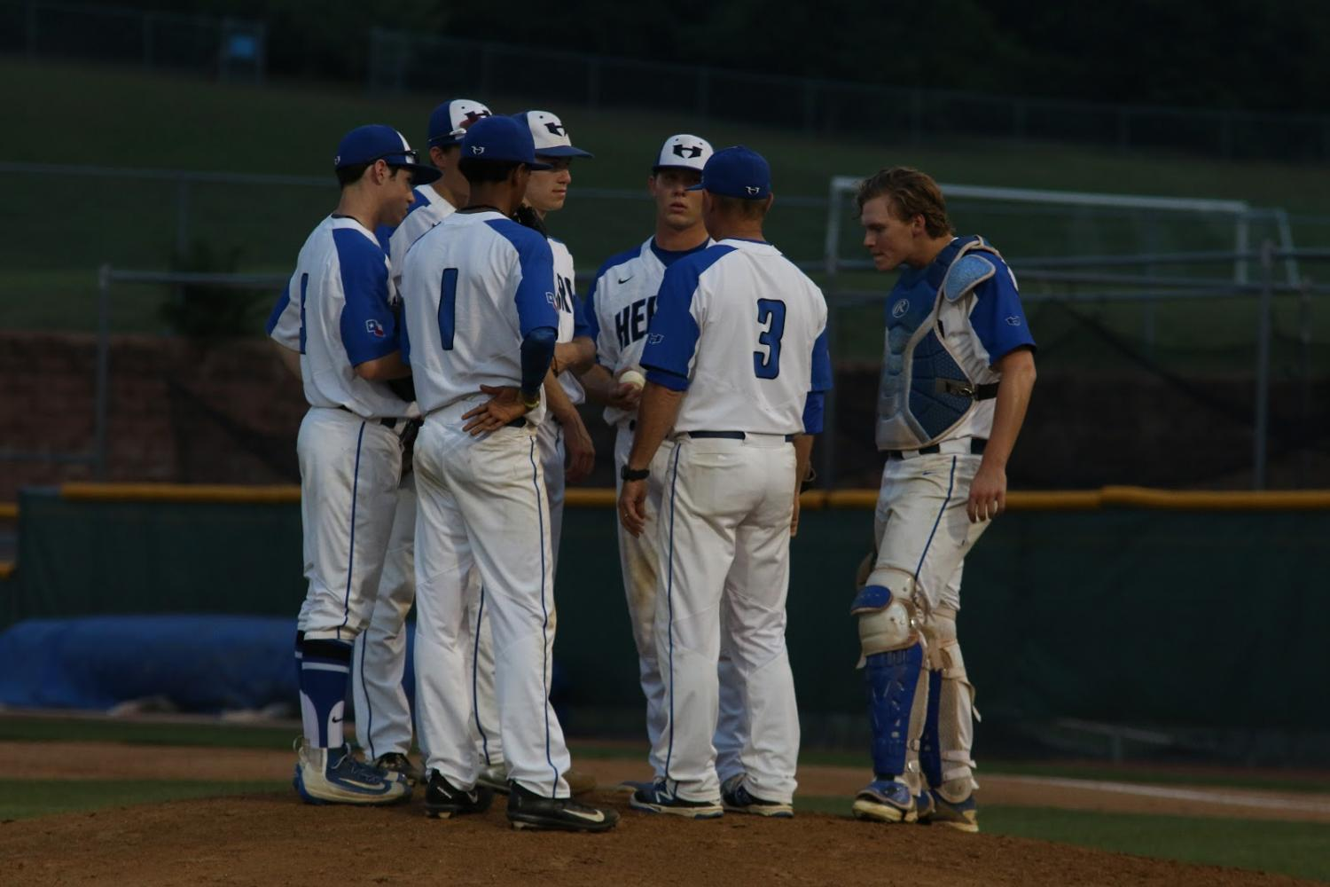 Coach+Stephen+Stone+and+players+huddle+to+talk+about+their+strategy.+Since+both+teams+were+tied+for+five+innings%2C+deliberating+their+options+for+a+winning+outcome+was+crucial.+