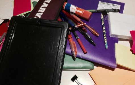 A collection of school supplies are laid out on a desk. Students are informed of what supplies are needed for each class on the first week of school.