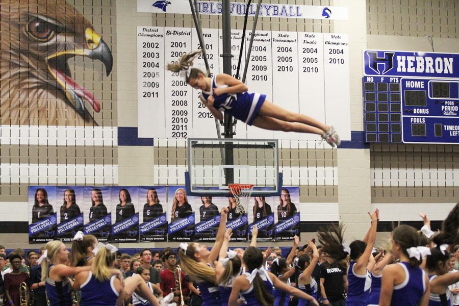 Junior Samantha Carmean performs a stunt with the cheer team.