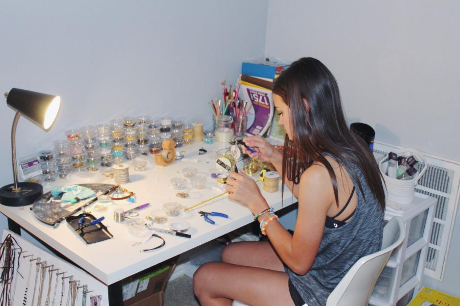 Junior Murphy Carlson works at her desk, creating jewelry for her customers. This is Carlson's first business and she runs it herself while being in school and extracurricular activities.