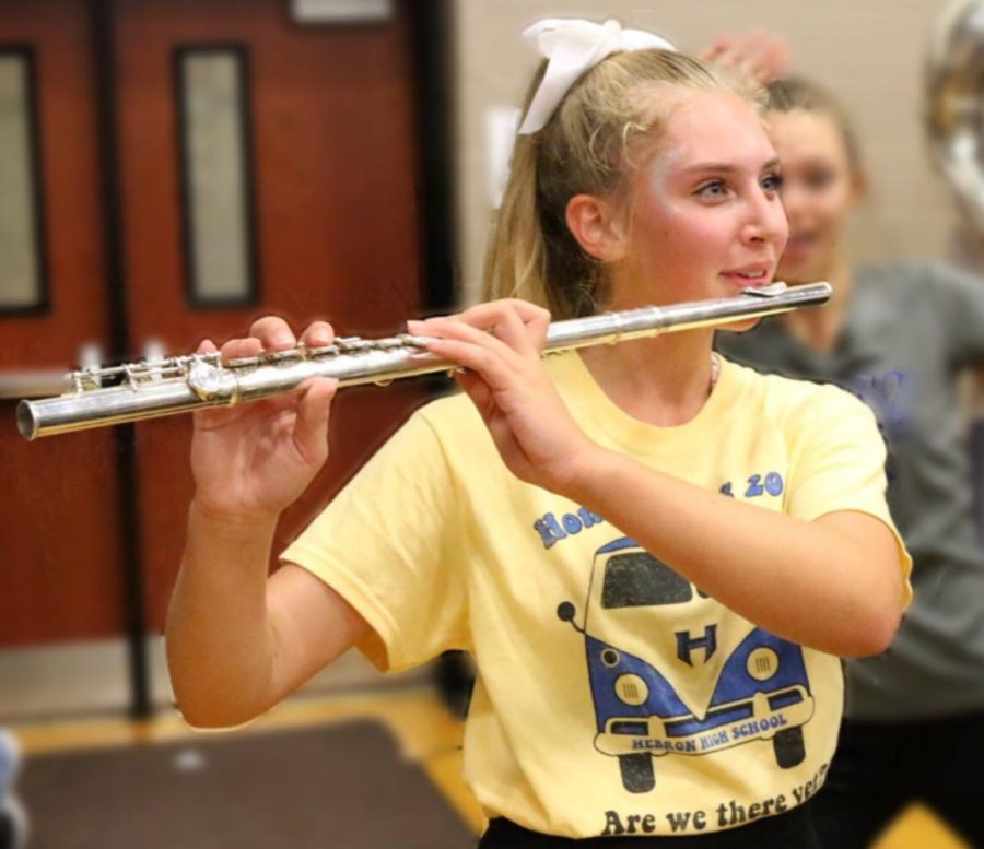 Freshman Jacquelyn Burrer plays the flute at the Homecoming pep rally. During pep rallies, Burrer has to switch from her cheer routine to her position in band.