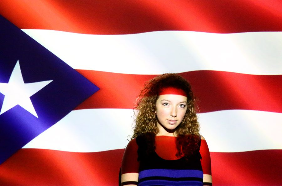 Senior Kierstin Hanifan stands in front of the Puerto Rican flag.