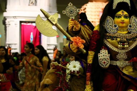 People dance around goddess Durga, goddess of war, during Garba. Goddess Durga is draped in fine clothing and jewelry.