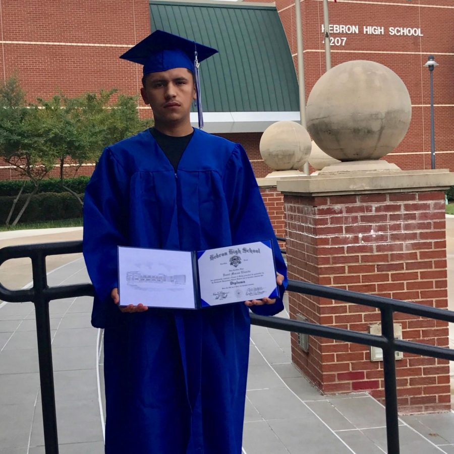 Elizardo holds up his diploma while wearing his cap and gown. Elizardo planned to work and earn enough money before he starts applying for colleges.