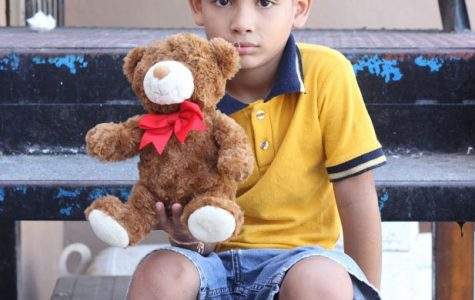 Nine-year-old Angel sits on the steps of the orphanage. He was playing with his toy bear.