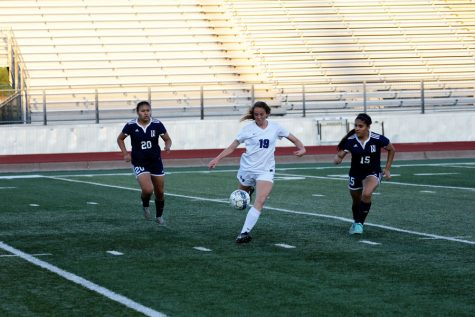 In the playoffs from last year, current junior Abby Glockzin dribbles between two opponents.