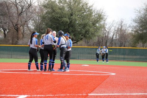 The softball team huddles around the pitcher