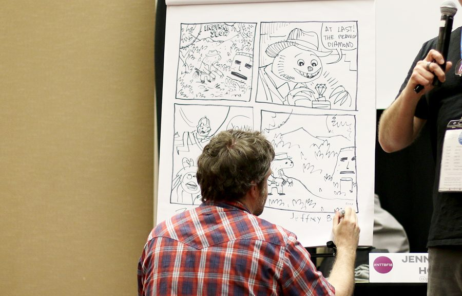 Cartoonist Jeffrey Brown signs his name on a four-panel comic as part of a competition. He was teamed up with Nathan Hale against Vera Brosgol and Jen Wang.