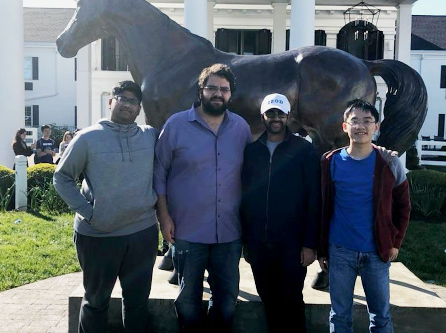 Junior Sunil Krish and Senior Andrew Nguyen stand for a picture with Debate Coach Cameron Vaziri and Hebron Debate alum Shaman Makani in front of the University of Kentucky.