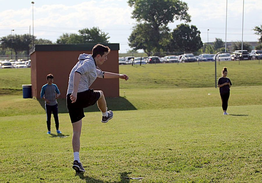 """Sophomore Conner Schaefer kicks the ball during a kickball game for his journalism class on May 9. He was working hard to make sure his team won the game. """"I was just trying to have fun out there and enjoy it as much as possible,"""" Schaefer said."""