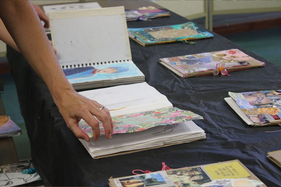 A woman flips through sketchbooks. Two tables were filled with these books.