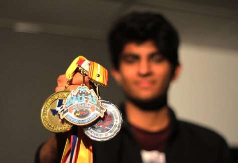 Senior Imran Abdul poses with medals he has earned throughout years of Taekwondo. Abdul was qualified as an International D-1 referee in 2015.
