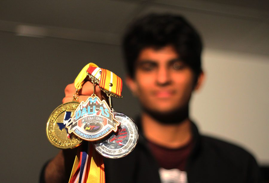 Senior+Imran+Abdul+poses+with+medals+he+has+earned+throughout+years+of+Taekwondo.+Abdul+was+qualified+as+an+International+D-1+referee+in+2015.