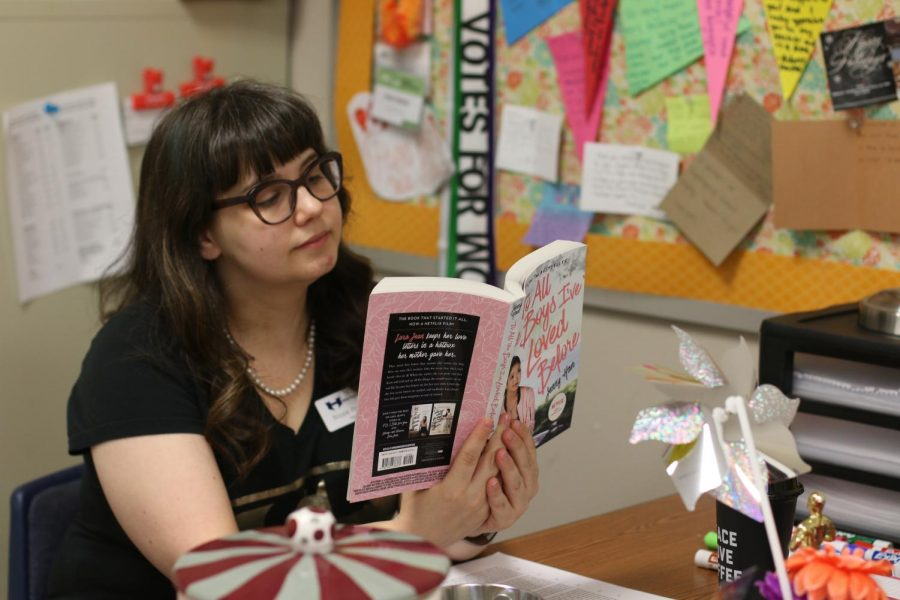 "English teacher Nicole Perkins reads at her desk before school hours. Despite living a self-appointed 'crazy, but in a sad way' life, Perkins consistently has a smile on her face and a witty remark on her tongue during her class periods. ""At the end of the day, we're all learning, and sometimes that's all you can ask for,"" Perkins said."