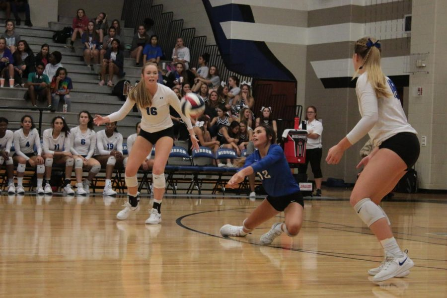 Junior Isabelle Ousby saves a serve.