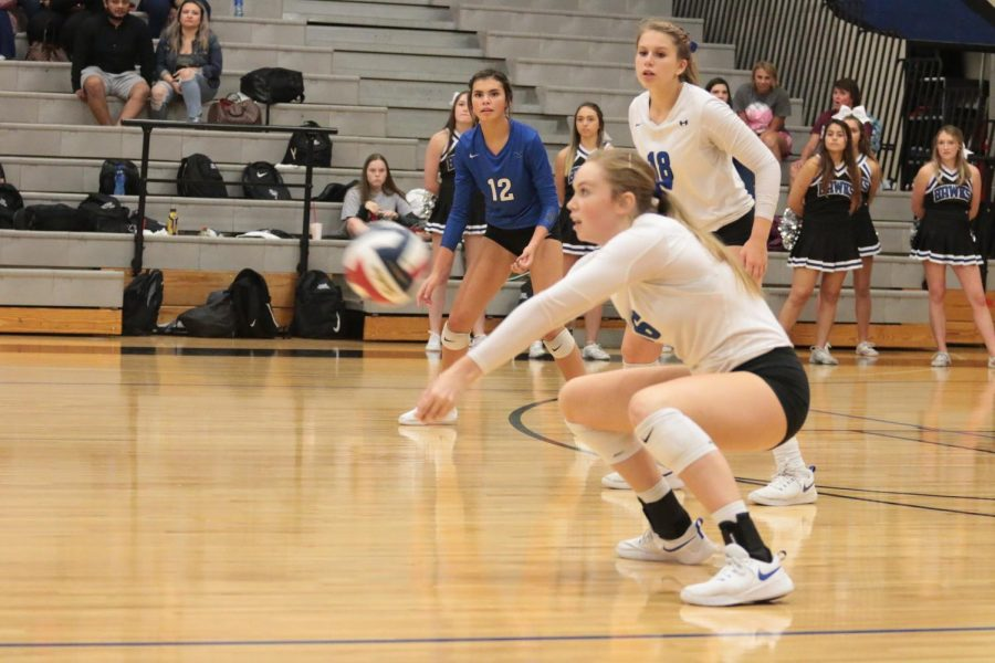 Senior Emma Clothier digs a serve and saves the point.