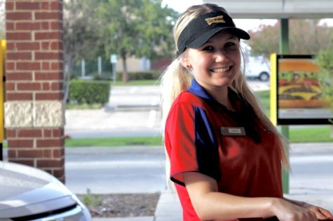 Junior Kellie Casburn poses at Sonic as she finishes delivering an order to a customer. Casburn said she wants to find a good job to support herself after she graduates.