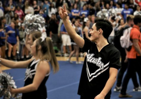 """Sophomore Nathan Drew cheers at the pep rally held on October 5th. The cheerleading team attends many school events to bring spirit and excitement to football games and more. """"I cheer at all the JV games: football, volleyball, basketball, all of those,"""" he said. """"We do pep rallies too, and if the school has a fundraiser event, we're there."""""""