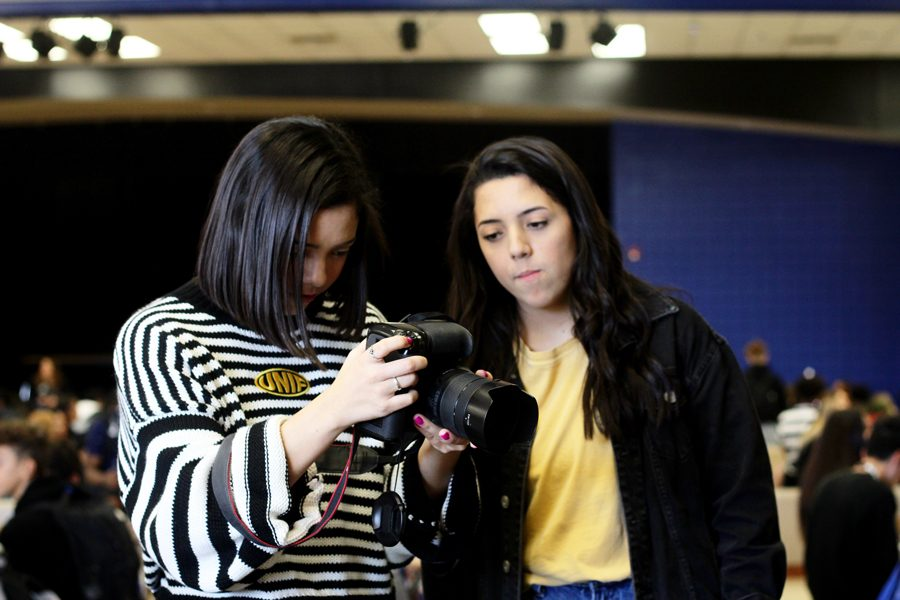 Seniors Krista Kummerl and Kayla Kummerl check the pictures they took for their Instagram account. They are looking for additional photographers to help add to the Instagram.