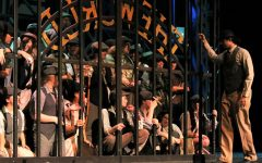 Newsies wait for the daily headline as Oscar (junior Krishna Nair) opens the gate. This rehearsal was a