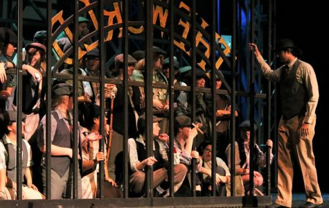 Newsies wait for the daily headline as Oscar (junior Krishna Nair) opens the gate. This rehearsal was a