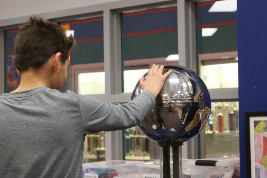 Elementary student experimenting with the Van de Graaf generator