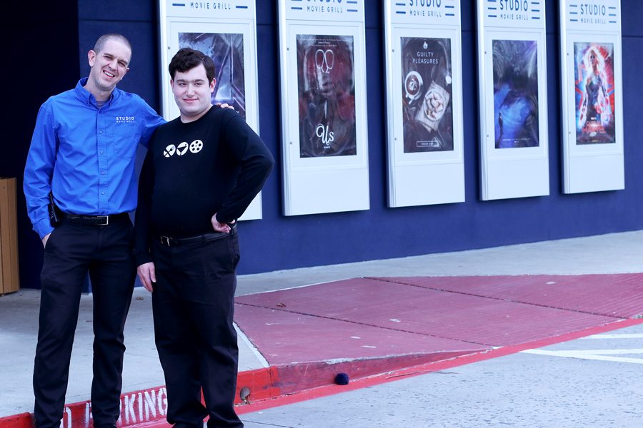 Studio Movie Grill manager Mike Dingess and employee Stephen Mentesana pose in front of the Studio Movie Grill at The Colony. Mentesana has been working there for three years.