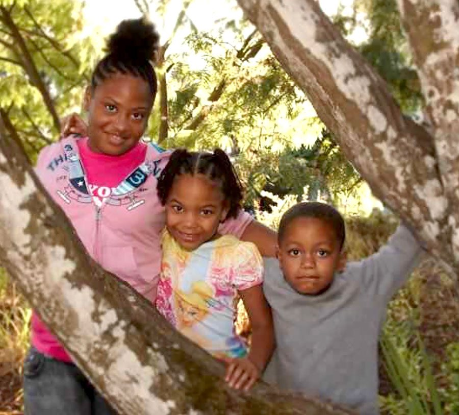 Rachaelle poses with her siblings Naomi Johnson and Giovonni Diaz behind a tree.
