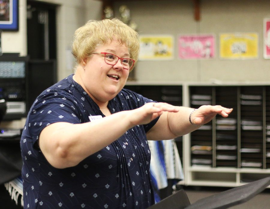 Choir director Rachel Forester conducts the Belle Chanson choir as they rehearse for the spring show on May 17 and 18. This show will be Forester's last choir concert she will be a part of.
