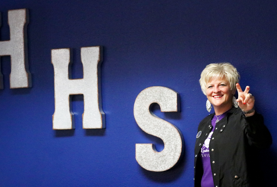 Principal Amy Boughton poses with the HHS wall in her office.  Boughton moved into her office the weekend after her appointment on June 20.