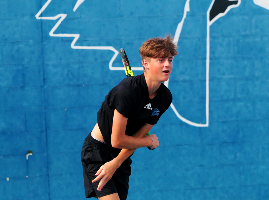 Freshman Dylan Bogan serves during a doubles match. The tennis team will play the Colony August 23.