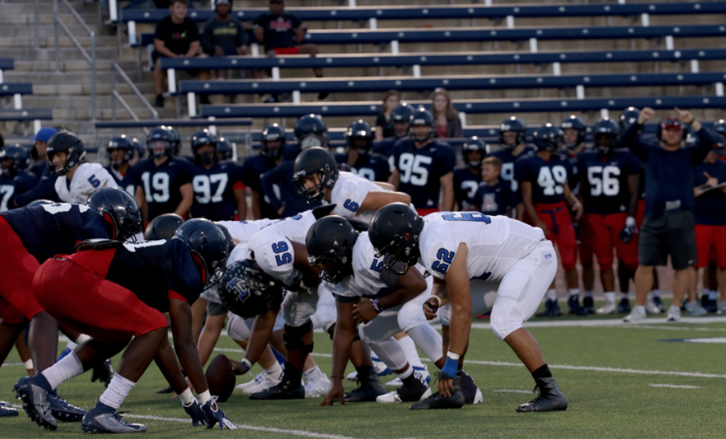 """The offensive linemen line up to snap the ball at the scrimmage on August 22. The scrimmage was the first time they have played against an opponent since last season. """"The goal as a team I feel like, is go to state and to play to our full potential,"""" senior Jeremiah Simon said."""