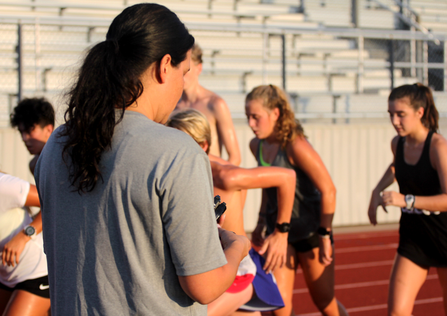 Coach Lana Soukup times the cross country times the team's sprints. The cross country team practices every Tuesday and Thursday morning.