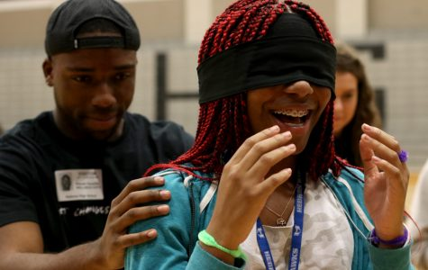 A Nike employee leads sophomore Breanna Britton, who is blindfolded, toward an obstacle course made of Nike shoe boxes.