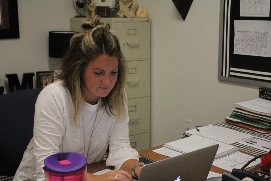 English teacher Megan Stinson grins while working on her laptop.
