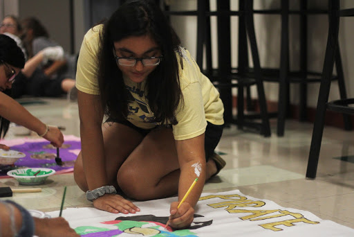 """Junior Asna Budwhani draws a pirate for the dress-up day poster for Thursday. Thursday's theme for under the sea was pirates vs. sailors. """"It was so much fun getting to work with my friends and painting,"""" Budwhani said."""