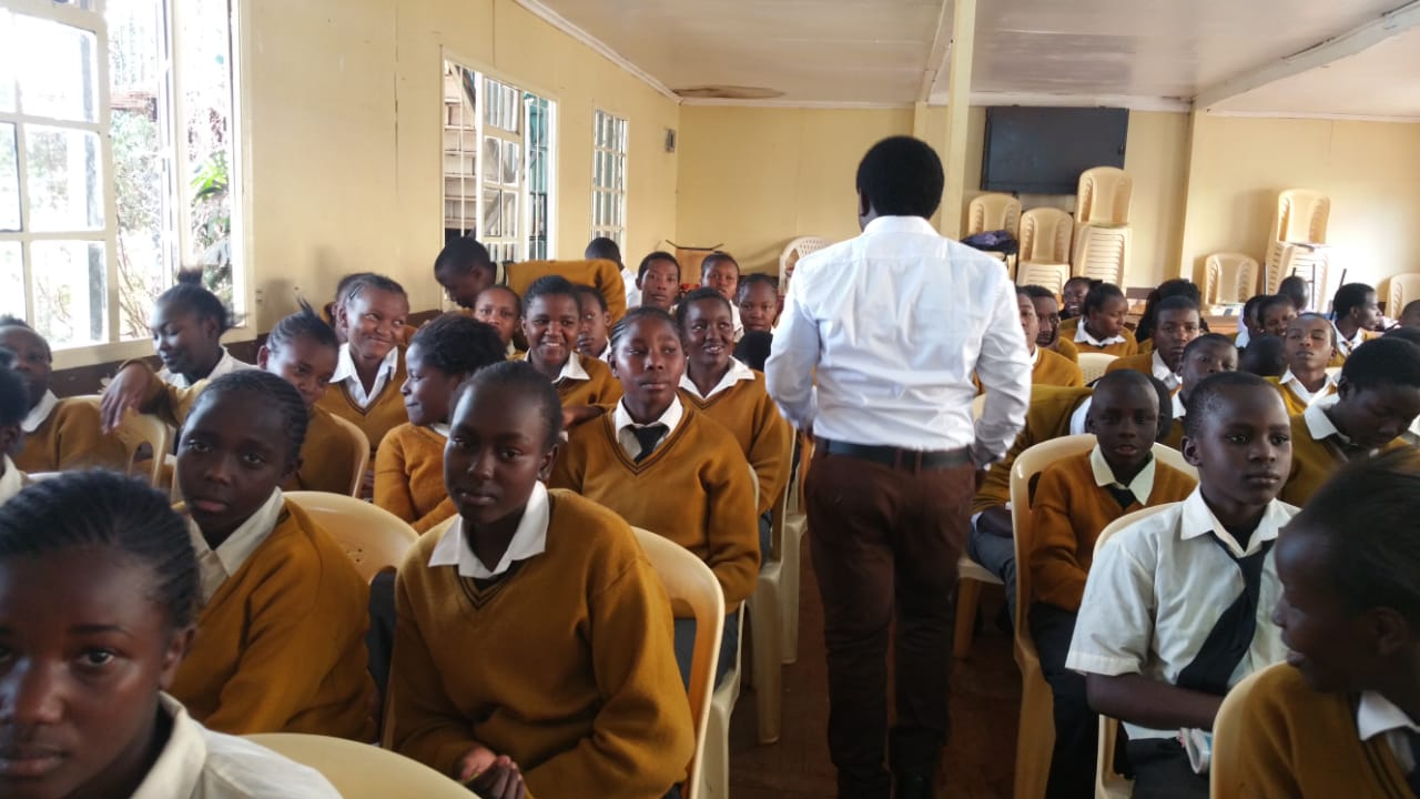 Students at New Dawn Education Center in Nairobi, Kenya sit in rows as their teacher begins class. They all have uniforms which is included in tuition costs.